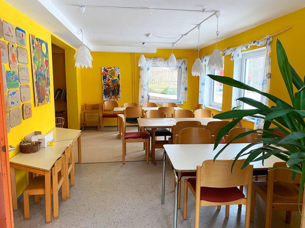 Tische mit Stühlen im großen Caféraum (gelb gestrichen)
