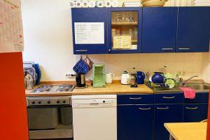 Küchenzeile (blaue Elemente) mit Geschirr und Elektrogeräten