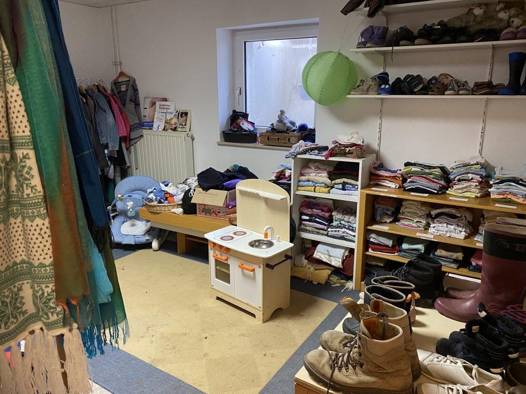 Raum mit verschiedenen Spenden wie Babykleidung, Schuhe, Babyspielzeug, usw.